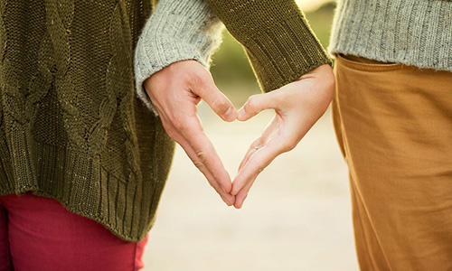 Par håller handen som ett hjärta