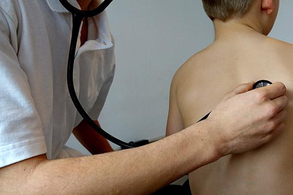 Läkare lyssnar på lungor med stetoskop