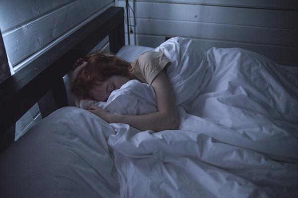 Kvinna som ligger i en säng