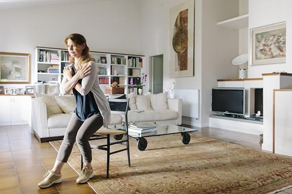 Kvinna gör en övning i sitt vardagsrum