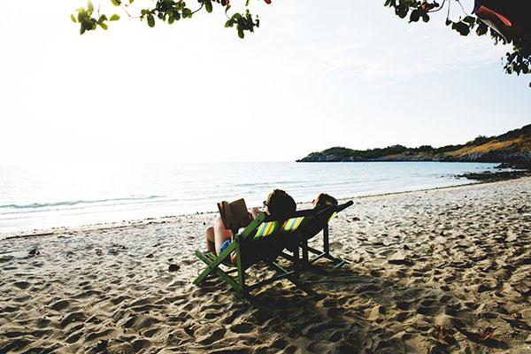 Två personer solar på en strand