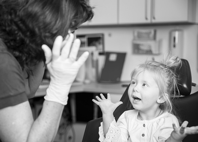 Tandläkare pratar med ett barn i tandläkarstolen