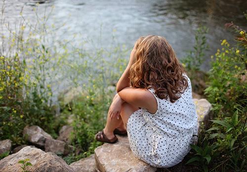 Tjej sitter på sten vid vattnet