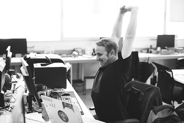 Man stretchar vid skrivbord
