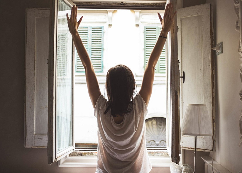 Kvinna står framför ett öppet fönster med utsträckta armar