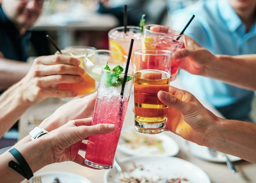 Människor skålar med olika drinkar