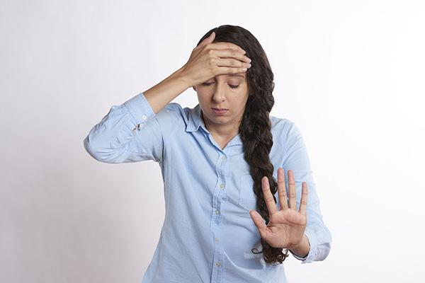 Kvinna som har ont i huvudet